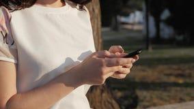 Ciérrese para arriba de las manos del ` s de la mujer usando el smartphone que se sienta en banco en parque en la puesta del sol  almacen de video