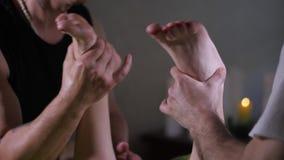 Ciérrese para arriba de las manos del ` s del terapeuta que dan masajes a pies femeninos La mujer joven que tiene se relaja en el almacen de metraje de vídeo