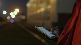 Ciérrese para arriba de las manos del trabajador de construcción usando el teléfono en el crepúsculo 4K almacen de video