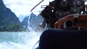 Ciérrese para arriba de las manos del ` un s del pescador que conducen el barco del longtail con un motor grande almacen de video