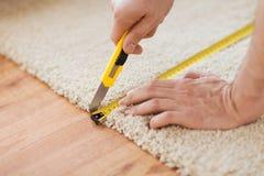Ciérrese para arriba de las manos del varón que cortan la alfombra Imagen de archivo libre de regalías