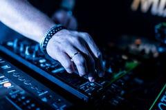Ciérrese para arriba de las manos de DJ que controlan una tabla de la música en un club nocturno fotos de archivo