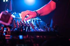 Ciérrese para arriba de las manos de DJ que controlan una tabla de la música en un club nocturno fotos de archivo libres de regalías
