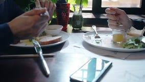 Ciérrese para arriba de las manos de dos hombres que desayunan junto en el café almacen de video