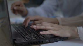 Ciérrese para arriba de las manos femeninas de la mujer con las pulseras que mecanografían en el teclado del ordenador portátil L almacen de metraje de vídeo