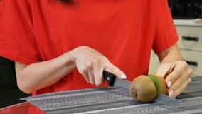 Ciérrese para arriba de las manos femeninas que cortan el kiwi fresco usando el cuchillo en la cocina Forma de vida sana y concep almacen de video