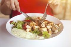 Ciérrese para arriba de las manos femeninas que cortan la ensalada deliciosa con el cuchillo y la bifurcación en el restaurante imagen de archivo