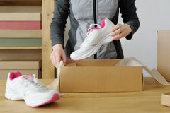 Ciérrese para arriba de las manos femeninas que embalan mercancías que se divierten Zapatos de los deportes Imagenes de archivo