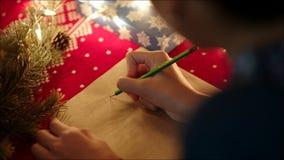 Ciérrese para arriba de las manos femeninas que escriben la letra de la Navidad con su wishlist el noche de los Años Nuevos metrajes