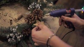 Ciérrese para arriba de las manos femeninas que pegan las estrellas en la guirnalda de la Navidad