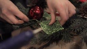 Ciérrese para arriba de las manos femeninas que pegan una hoja artificial en la guirnalda de la Navidad