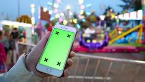 Ciérrese para arriba de las manos femeninas que sostienen el teléfono elegante con una pantalla verde