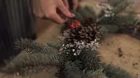 Ciérrese para arriba de las manos femeninas que tejen la guirnalda que arregla la decoración