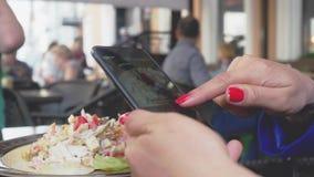 Ciérrese para arriba de las manos femeninas que toman la foto de la comida de la ensalada de los mariscos 4k, 3840x2160 metrajes