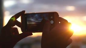 Ciérrese para arriba de las manos femeninas que toman la foto de la opinión de la ciudad de la puesta del sol con su teléfono móv Imágenes de archivo libres de regalías