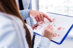 Ciérrese para arriba de las manos femeninas y masculinas que señalan en el documento de negocio mientras que lo discute Imagen de archivo libre de regalías