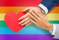 Ciérrese para arriba de las manos gay masculinas de los pares con el corazón rojo Imágenes de archivo libres de regalías