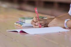 Ciérrese para arriba de las manos jovenes del estudiante que escriben en el cuaderno Fotos de archivo