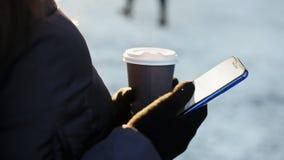 Ciérrese para arriba de las manos de la muchacha en guantes, usando smartphone y el café de consumición, invierno soleado almacen de metraje de vídeo