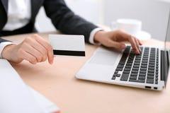 Ciérrese para arriba de las manos de la mujer de negocios usando tarjeta y el ordenador portátil de crédito imagenes de archivo