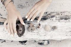Ciérrese para arriba de las manos de la mujer que sostienen los osículos en fondo de madera Fotos de archivo