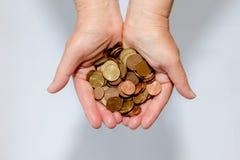 Ciérrese para arriba de las manos de la mujer que sostienen monedas euro del dinero fotografía de archivo