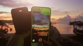 Ciérrese para arriba de las manos de la mujer que toman el vídeo con el teléfono móvil de la puesta del sol mientras que se sient metrajes