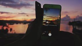 Ciérrese para arriba de las manos de la mujer que toman la foto con el teléfono móvil de la puesta del sol mientras que se sienta almacen de metraje de vídeo
