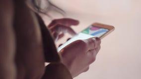 Ciérrese para arriba de las manos de la mujer usando el teléfono elegante en la ciudad de la noche con las luces del bokeh primer almacen de metraje de vídeo