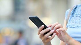 Ciérrese para arriba de las manos de la mujer usando un teléfono elegante metrajes