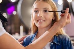 Ciérrese para arriba de las manos de los artistas de maquillaje que aplican el rimel Imágenes de archivo libres de regalías