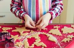 Ciérrese para arriba de las manos de los childs que hacen las galletas de la Navidad Foto de archivo libre de regalías