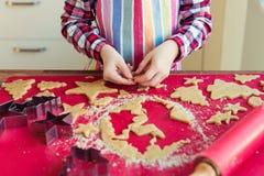 Ciérrese para arriba de las manos de los childs que hacen las galletas de la Navidad Imagen de archivo libre de regalías