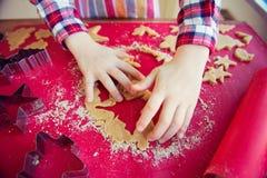 Ciérrese para arriba de las manos de los childs que hacen las galletas de la Navidad Imágenes de archivo libres de regalías