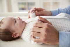 Ciérrese para arriba de las manos de los hijos de Holding Newborn Baby del padre en cuarto de niños fotografía de archivo