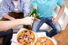 Ciérrese para arriba de las manos masculinas con la cerveza y la pizza en casa Imagen de archivo libre de regalías