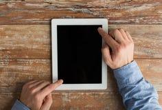Ciérrese para arriba de las manos masculinas con PC de la tableta en la tabla Imagen de archivo libre de regalías