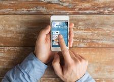 Ciérrese para arriba de las manos masculinas con smartphone en la tabla Foto de archivo libre de regalías