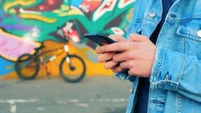 Ciérrese para arriba de las manos masculinas con un smartphone con una bici y una pintada en el fondo almacen de metraje de vídeo