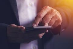 Ciérrese para arriba de las manos masculinas del hombre de negocios usando el teléfono móvil Imagen de archivo