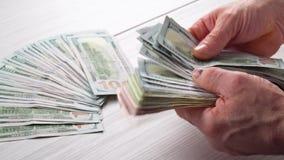 Ciérrese para arriba de las manos masculinas que cuentan billetes de banco del dólar de EE. UU. en la tabla en frente un contable almacen de video