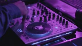 Ciérrese para arriba de las manos masculinas que dan vuelta al mezclador de DJ de los botones metrajes