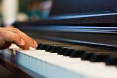 Ciérrese para arriba de las manos masculinas que juegan el piano. Foto de archivo