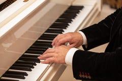 Ciérrese para arriba de las manos masculinas que juegan el piano Forma horizontal fotografía de archivo libre de regalías