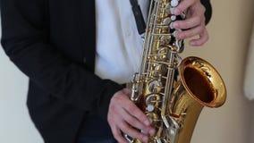 Ci?rrese para arriba de las manos masculinas que tocan el saxof?n almacen de metraje de vídeo