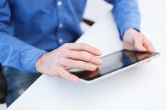 Ciérrese para arriba de las manos masculinas que trabajan con PC de la tableta Foto de archivo libre de regalías