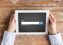Ciérrese para arriba de las manos masculinas usando el navegador en la PC de la tableta Fotos de archivo