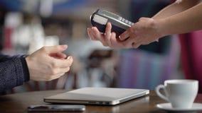 Ciérrese para arriba de las manos masculinas y femeninas que hacen proceso del pago cashless en restaurante Camarera que da a la  almacen de metraje de vídeo