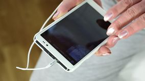 Ciérrese para arriba de las manos mayores de la mujer usando el smartphone blanco almacen de video