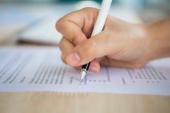 Ciérrese para arriba de las manos que completan el formulario de inscripción del empleo de una pluma Imágenes de archivo libres de regalías